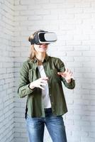 erstaunte Frau in VR-Brille, die auf weißem Backsteinmauerhintergrund steht foto