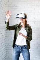 Frau in VR-Brille, die auf weißem Backsteinmauerhintergrund steht foto