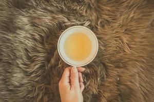 weibliche Hand, die eine Tasse grünen Tee auf dem flauschigen braunen Pelzplaid hält. foto