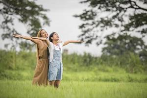 Mutter und Tochter stehen glücklich auf der Wiese foto