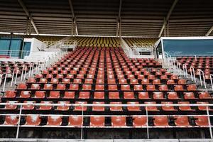 Rote leere und alte Plastiksitze im Stadion. foto