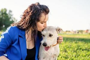 junge attraktive Frau, die ihren Hund küsst foto