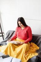Frau, die zu Hause ein Buch liest, sitzt auf dem Sofa und lächelt vor Freude foto