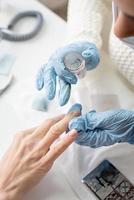 Maniküremeister in Maske und Handschuhen beim Stempeln für den Kunden foto