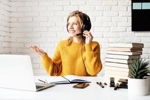 junge lächelnde Frau in schwarzen Kopfhörern, die online mit Laptop studiert? foto