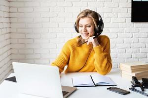junge Frau in schwarzen Kopfhörern, die online mit Laptop studiert? foto