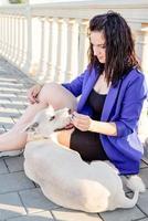 junge Frau spielt mit ihrem Hund im Park foto