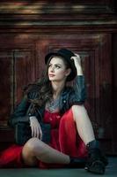 junge schöne brünette frau mit rotem kurzen kleid und schwarzem hut foto