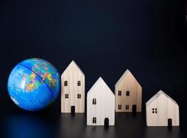 Modell-Holzhäuser und Miniatur-Globen leer auf schwarzem Hintergrund. foto