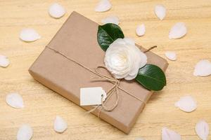 Geschenkbox mit leerem Etikett und weißer Kamelienblüte auf dem Tisch foto