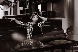junge Frau mit kurzen Haaren in einer Bar legte ihre Beine auf den Tisch foto
