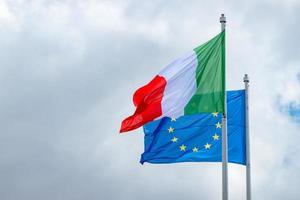 Flaggen der italienischen und europäischen Union wehen gegen einen bewölkten Himmel foto