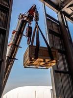 der Kran, der eine Holzkiste mit radioaktivem Paket zum Werk trägt foto