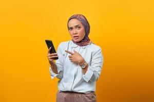 überraschte asiatische Frau beim Zeigen des Smartphones auf gelben Hintergrund foto