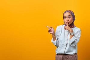 schöne asiatische frau signalisiert zum schweigen und zeigt zur seite foto