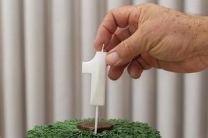 Hand des weißen Mannes, die 1-Jahres-Kerze auf Kindergeburtstagskuchen setzt foto