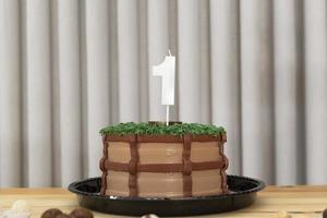 einjährige weiße Kerze auf Kuchen im Landhausstil dekoriert foto