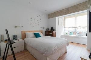 schönes Schlafzimmer in Weiß mit Tageslicht, Holzboden und Sofa foto