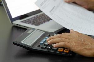 Geschäftsmann mit Taschenrechner an einem Schreibtisch. Unternehmensfinanzierung, Steuern, foto