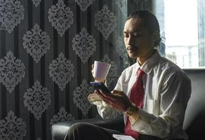 entspannter asiatischer mann, der kaffee trinkt, während er ein handy für die arbeit benutzt foto