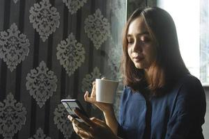 entspannte asiatische frau, die kaffee trinkt, während sie ein handy für die arbeit benutzt foto