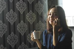 Lächelnde asiatische Frau, die Kaffee trinkt, während sie ein Handy für die Arbeit benutzt foto