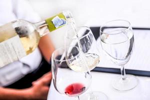Verkostung von Weißwein in ein Glas gießen, Wein aus der Weinflasche einschenken foto
