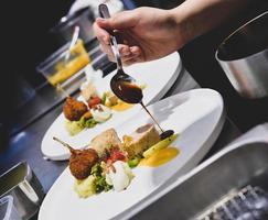 Koch bereitet Essen in der Küche zu, Koch kocht, Koch dekoriert Gericht foto