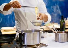 Koch kocht Spaghetti in der Küche foto