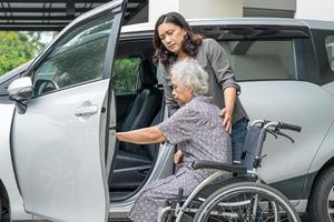 helfen und unterstützen Sie asiatische ältere Frau, um zu ihrem Auto zu gelangen. foto