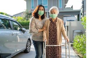 Asiatische Seniorin geht mit einem Wanderer, der eine Maske trägt, um das Coronavirus zu schützen. foto