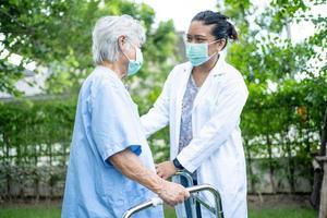 Hilfe und Pflege asiatische Seniorin verwendet Gehhilfe im Park foto