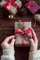 Weihnachtsgeschenke verpacken. Frau bindet Schleife auf der Box. foto