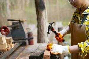 Frau stehende Bauarbeiterin, die Nagel in das Holzbrett hämmert foto