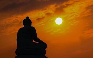 Silhouette Buddha auf Sonnenuntergang Hintergrund scheint von hinten foto