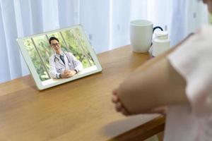 Patient konsultieren wegen Gelenkschmerzen online einen Arzt foto