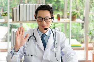 asiatischer Arzt berät den Patienten per Online-Videoanruf foto