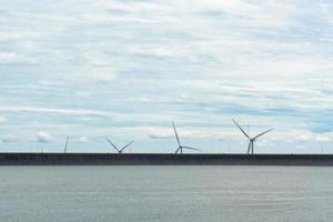 Windkraftanlage zur Erzeugung von erneuerbarem Strom und der Damm foto