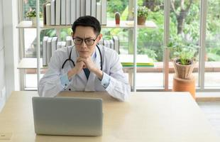 junger asiatischer Arzt, der Computer im Krankenhausbüro verwendet foto