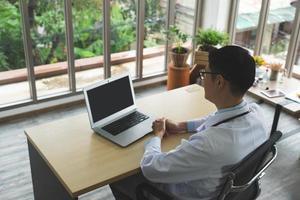 junger asiatischer Arzt, der mit Computer im Krankenhausbüro arbeitet foto