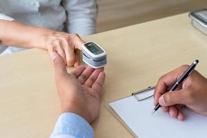 Arzt misst die Sauerstoffsättigung mit einem Pulsoximeter-Gerät foto