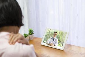 älterer Patient konsultieren online einen Arzt über Schulterschmerzen foto