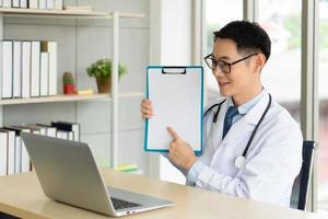 asiatischer Arzt berät den Patienten online foto