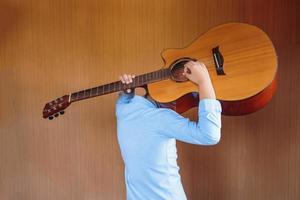 Junge, der mit Spaß klassische Gitarre spielt foto