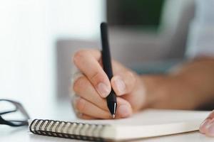 Mannhände schreiben auf den Notizblock, Notizbuch mit Kugelschreiber foto