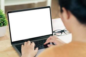 Frau tippt Laptop-Tastatur mit weißem leerem Bildschirm auf dem Tisch foto