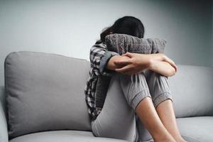 Traurige Frau sitzt auf der Couch und versteckt ihr Gesicht auf einem Kissen foto