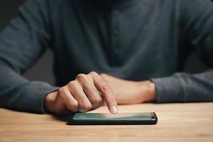 Mann, der ein Smartphone auf dem Holztisch benutzt, sucht, surft foto