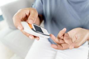 Frau überprüft den Blutzuckerspiegel durch digitales Blutzuckermessgerät foto