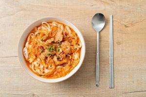 koreanische Udon-Ramen-Nudeln mit Schweinefleisch in Kimchi-Suppe foto